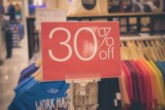 Rood verkoopteken 30 percentenkorting op vage achtergrond in een winkelcomplex van Bali, Indonesië, Azië Royalty-vrije Stock Foto's