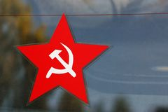 Rood vijf-gerichte ster met sikkel en hamerembleem stock afbeeldingen
