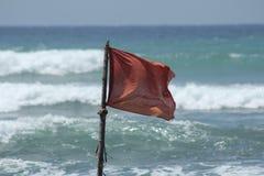 Rood vlaggevaar tijdens een onweer op de oceaan Royalty-vrije Stock Afbeeldingen