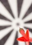 Rood vliegend pijltje aan dartboard Stock Afbeeldingen