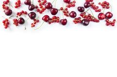 Rood voedsel bij grens van beeld met exemplaarruimte voor tekst Rood voedsel Rijpe rode aalbessen en kersen op een witte achtergr Stock Afbeeldingen