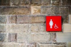 Rood vrouwelijk toilet en gehandicapt toegankelijk teken op de oude steenbakstenen muur stock fotografie