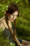 Rood zijaanzicht van een mooie jonge vrouw met een nadenkende blik, Stock Afbeeldingen