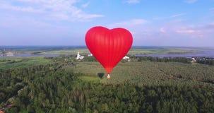 Roodgloeiende luchtballon in de vorm van een hart in de lucht Mening rond, lucht stock footage