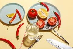 Roodgloeiende peper, tomaten, rozemarijn en kruiden op ligth-gele achtergrond Dien het plaatsen in Hoogste mening stock fotografie