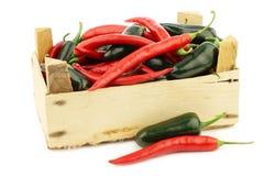 Roodgloeiende Spaanse peper en groene paprika'sjalapeno in een houten doos Royalty-vrije Stock Afbeeldingen