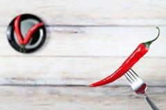 Roodgloeiende Spaanse peperpeper met waterdalingen op vork Stock Afbeelding
