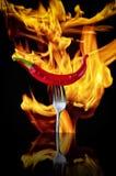 Roodgloeiende Spaanse peperpeper op vork over zwarte achtergrond Roodgloeiende Spaanse peperpeper op een zilveren uitstekende vor royalty-vrije stock foto's