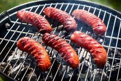 Roodgloeiende worsten met kruiden en rozemarijn op een grill Royalty-vrije Stock Foto's