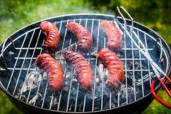 Roodgloeiende worsten met rozemarijn op een grill Stock Foto's