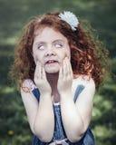roodharig Kaukasisch meisje die in blauwe kleding grappige enge dwaze gezichten maken royalty-vrije stock foto's