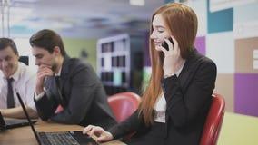 Roodharig meisje die op de telefoon op het kantoor spreken stock video