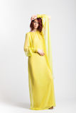 Roodharig meisje in lange elegante gele kleding Stock Foto's