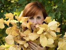 Roodharig meisje met gele bladeren Royalty-vrije Stock Foto