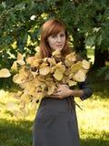 Roodharig meisje met gele bladeren Stock Afbeeldingen