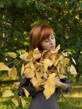 Roodharig meisje met gele bladeren Stock Foto's