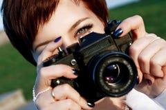 Roodharig meisje met groene ogen die beeldencamera in het stadspark nemen Stock Afbeelding