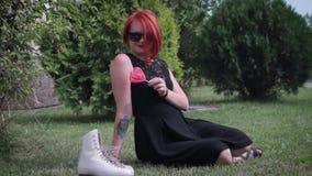 Roodharig meisje in zwarte kleding die zich op de stoep vooraan bevinden stock footage