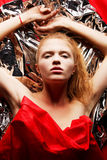 Roodharig model in rood over zilveren folie royalty-vrije stock foto