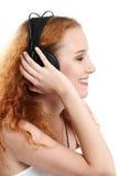 Roodharige die aan muziek luistert Stock Afbeelding