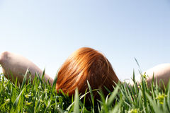 Roodharige die in Gras legt dat omhoog eruit ziet Stock Afbeelding
