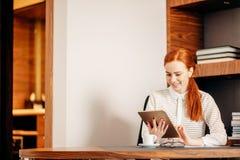 Roodharige die jonge vrouwelijke manager glimlachen die moderne digitale tablet gebruiken op kantoor royalty-vrije stock foto