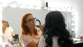 Roodharige stilistgrimeur die modieuze avondsamenstelling van model met lang zwart haar in schoonheidssalon doen stock videobeelden