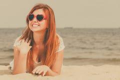 Roodharige volwassen vrouw die op strand liggen royalty-vrije stock afbeeldingen