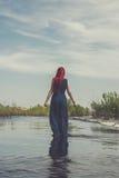 Roodharige vrouw die in de rivier lopen stock afbeelding