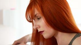 Roodharige vrouw die haar haar met een ijzer in evenwicht brengt vóór de spiegel stock footage