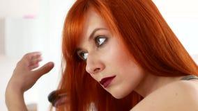 Roodharige vrouw die haar haar met een ijzer in evenwicht brengt vóór de spiegel stock video
