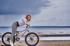 Roodharige vrouw op middelbare leeftijd in sportkleding op een fietsgang op de zandige kust van een grote rivier stock afbeeldingen
