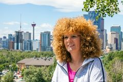 Roodharige vrouw voor de horizon van Calgary stock afbeeldingen