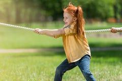 Roodharigekind die kabel trekken stock fotografie