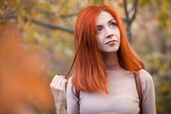 Roodharigemeisje in de herfst stock afbeeldingen