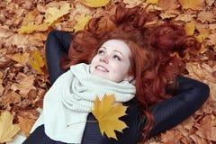 Roodharigemeisje die op bladeren in stadspark liggen, dalingsseizoen stock foto's