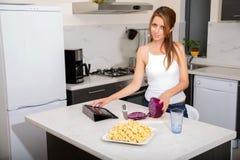 Roodharigemeisje het snijden in keuken wat betreft tabletpc royalty-vrije stock foto