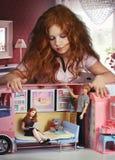 Roodharigemeisje het spelen in een poppenhuis Stock Foto