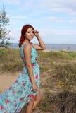 Roodharigemeisje in lange kleding die zich bij de kust bevinden Stock Afbeelding