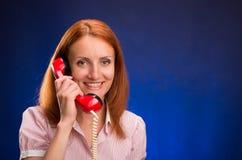 Roodharigemeisje met rode telefoon Stock Afbeeldingen