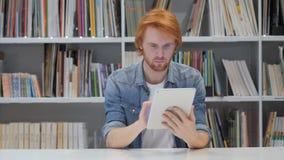 Roodharigemens die Internet op tabletpc doorbladeren stock videobeelden