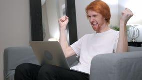Roodharigemens voor succes wordt opgewekt, die aan laptop werken die stock footage