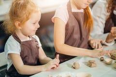 Roodharigemoeder en twee dochtervorm met klei, aardewerkkinderen stock fotografie