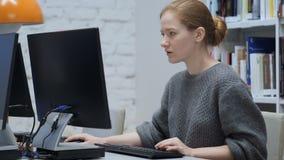 Roodharigevrouw die aan computer in bureau werken stock footage