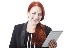 Roodharigevrouw die aangezien zij haar tablet leest lachen stock foto's