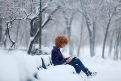 Roodharigevrouw die een boek in de sneeuw lezen stock foto's
