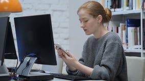 Roodharigevrouw die Internet online op smartphone doorbladeren stock video