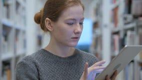 Roodharigevrouw die Internet op tablet doorbladeren op het werk stock video