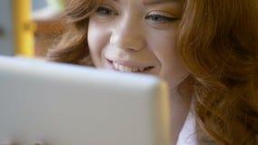 Roodharigevrouw die tabletcomputer in koffie met behulp van stock video