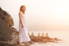 Roodharigevrouw die zich op de kust op strand bevinden Royalty-vrije Stock Fotografie
